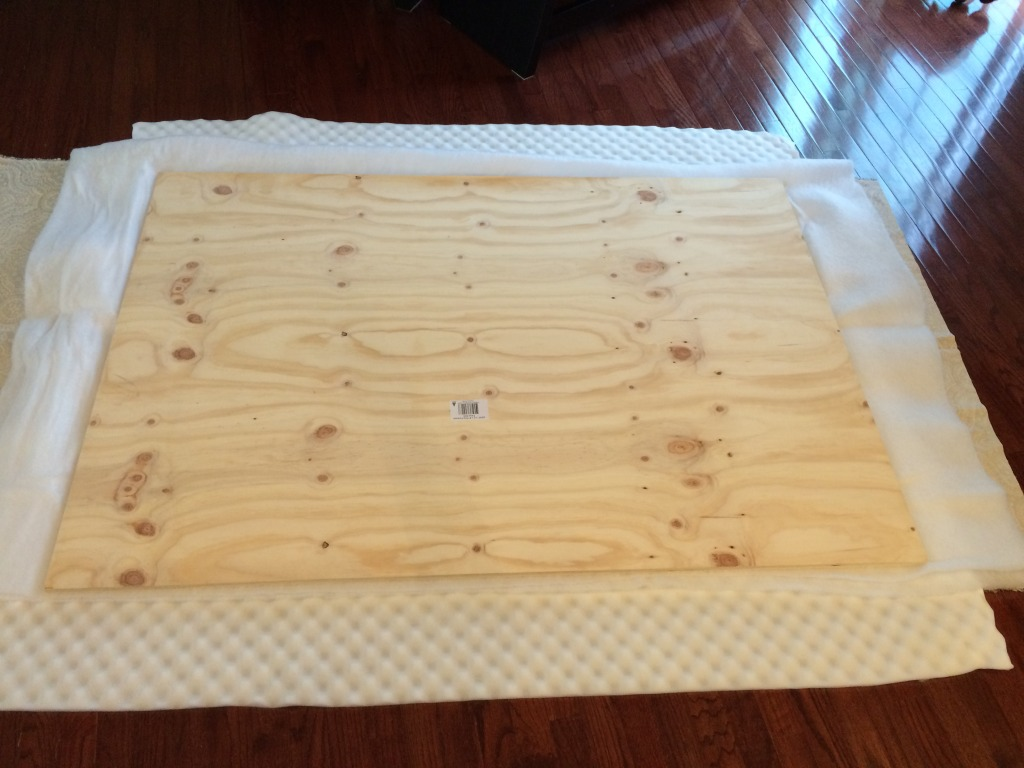 The bottom layer is the fabric turned the wrong way. Then the foam mattress pad and the wood with the batting glued on.